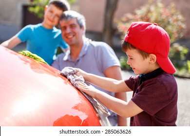 Little boy in cap washing car with dad and brother, fun with family