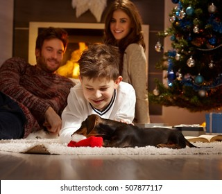 Little boy caressing and playing with dachshund puppy received for christmas.