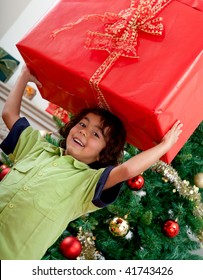 Little boy carrying a Christmas present and smiling
