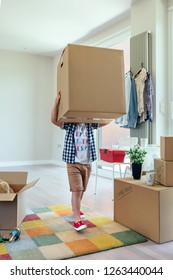 Little boy carrying very large moving box in the living room