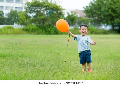 Little boy catch with flying balloon