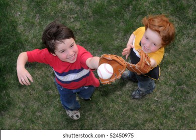 A little boy catches a fly ball during a baseball game