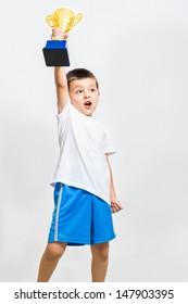 Little boy celebrates his golden trophy