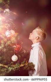 Little boy celebrating the magic of Christmas standing looking up into a decorated Xmas tree with a glowing light suffusing the air