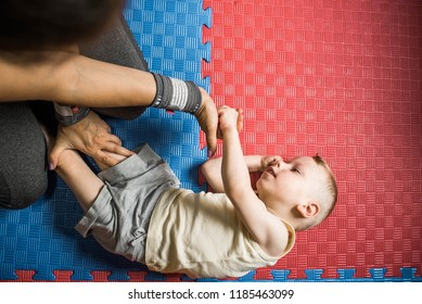 Little boy with cerebral palsy has musculoskeletal therapy by doing exercises on floor mat. Child give hand therapist