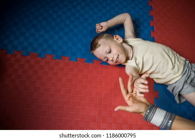 Little boy with cerebral palsy has musculoskeletal therapy by doing exercises on floor mat. Hand holding hand therapist . Child smile