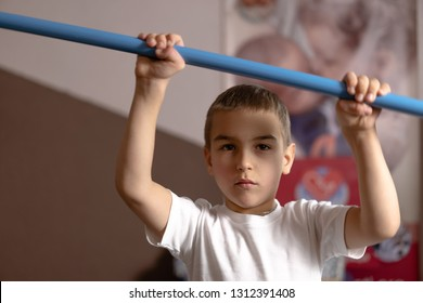 little boy with cerebral palsy has musculoskeletal therapy by doing exercises in body fixing. Load on hands with weights