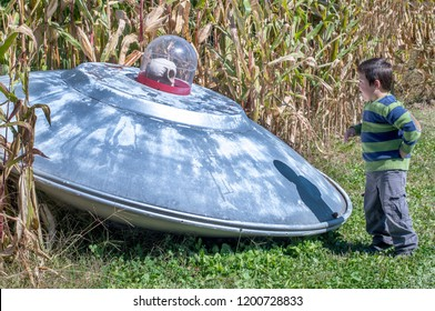 little boy checks out a flying saucer complete with alien, that landed just outside a Michigan USA corn field
