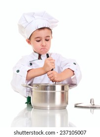 Little boy chef with ladle stirring in the pot by both hands isolated on white