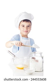 Little boy in chef's cap and apron adds spoonful of flour into the eggs to knead the dough