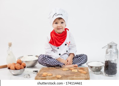 Little boy with chefs hat, preparing cookies