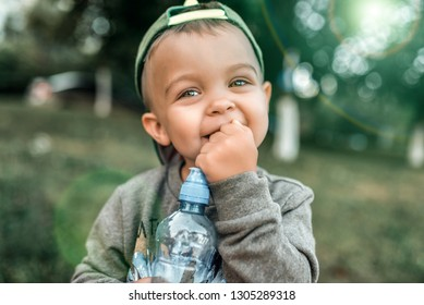 Little boy child 2-4 years old, close-up portrait, happy laughing in his hands holding a bottle of water. In the summer in the city in the fresh air. A sincere look with eyes.