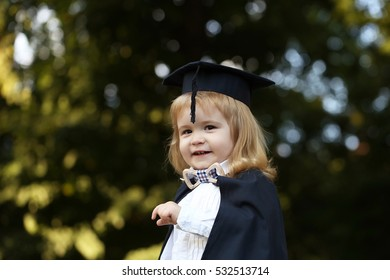 Little boy child in black academic gown and squared school hat and bow tie with blonde hair on smiling face standing outdoor on green natural background