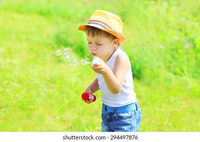 Little boy child blowing soap bubbles outdoors in sunny summer day 7a49bcb6fb36