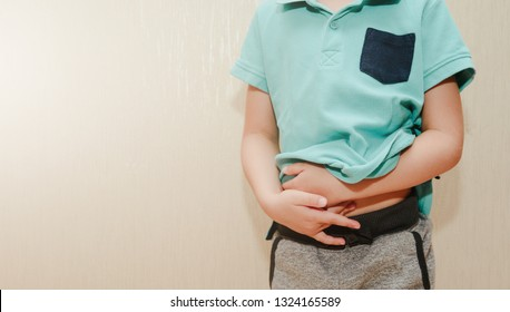 A little boy, the child is holding his belly. Baby's medication and health concept. Stomach ache. Suffering a young child. Food poisoning, abdominal pain. Health problems in children.