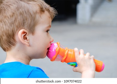 A little boy child holds a toy microphone in hand and sings, opening mouth.