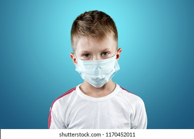 Little boy, a child in a medical mask on a blue background. The concept of an epidemic, influenza, protection from disease, vaccination.