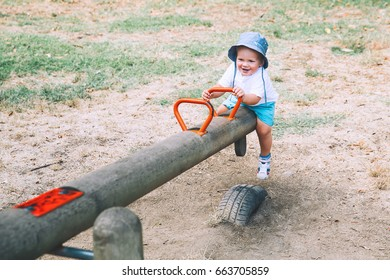 Little boy child playing on a playground. Cute smiling fashionable kid on swing. Happy family on playground at summer day in a park. Leisure, childhood and people concept.
