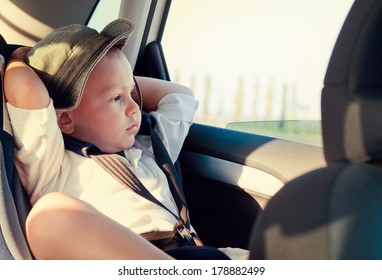 Little boy in a child safety seat sitting patiently in the back of a car with his hands behind his head staring out of the window