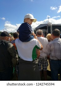 Little boy child sitting on his father shoulders in crowd of people back view in public festival event in summer day.
