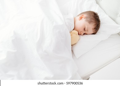 Little boy child sleeping in bed. Hugging his favourite teddy bear. Covered with white duvet
