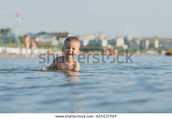 Little boy child swimming in the sea. bathing in sea water. Summer vacation holiday vacation.