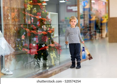 Little boy chooses gifts for the New Year on the background of shop windows
