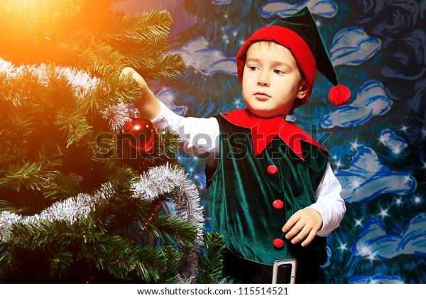 Little boy in Christmas elf costume posing over christmas background.