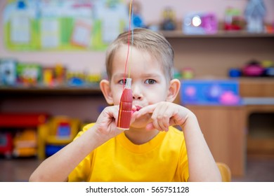 The little boy in the classroom with the speech therapist . The use of special tools for speech correction.