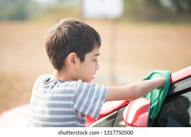 Little boy cleaning car