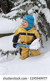 Little boy cleans snow with a toy shovel