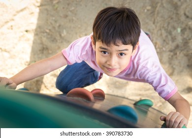 Little boy climbing up brave at playground