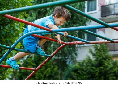 Little boy climbing on jungle gym without rope and helmet on playground, dangerous