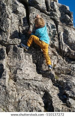 little boy climbing on rock facing stock photo edit now 510137272