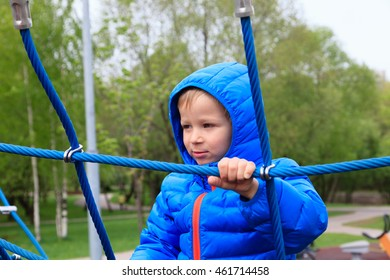 little boy climbing on the web in playground