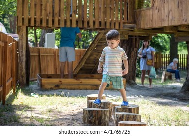 Little boy climbing on a wooden playground in a rope park. Kid play outdoors on warm sunny summer day.