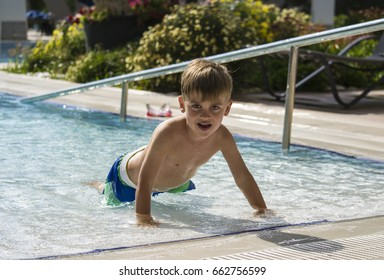 Little boy climbing out of a swimming pool