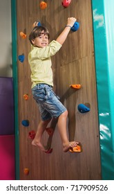 Little Boy Climbing a Rock Wall Indoor. Children's Entertainment Sports Soft Ground.