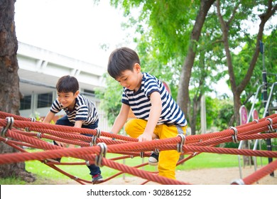Little boy climbing rope at playground