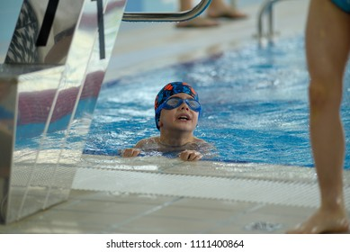 Little boy climbs out of the pool