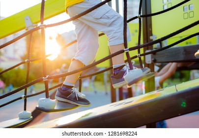 little boy climbs up the stairs on the playground. the child confidently climbs the staggering stairs against the background of sunlight. active development