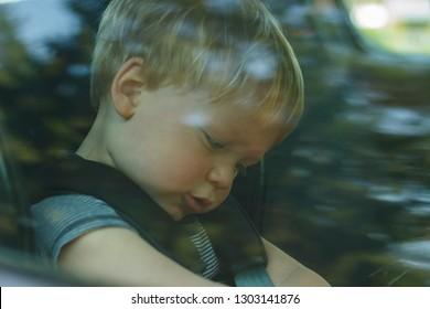little boy close up portrait through the car window glass.