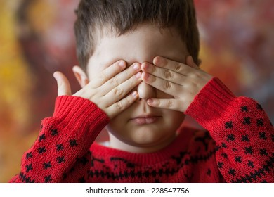 little boy closed his eyes with hands, abstract background