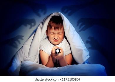 Little boy closing eyes of nigh fears hiding under the blanket