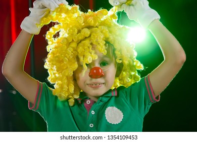 Little boy clown. Child in a clown wig with a red nose close up