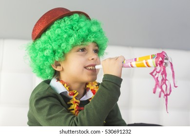 Little boy in clown wig having fun celebrating birthday or carnival. Positive emotions