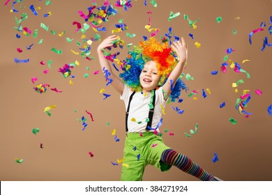 Little boy in clown wig jumping and having fun celebrating birthday. Brazilian Carnival. Venice Carnival. child throws up a multi-colored tinsel and confetti. Birthday boy. Positive emotions.
