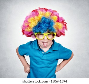 Little boy with clown wig mocking isolated on gray background