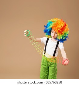 Little boy in clown wig smiling and playing with Magic Spring. Happy clown boy with large colorful wig. Birthday boy. Little clown boy with colorful hair and Slinky spring toy.