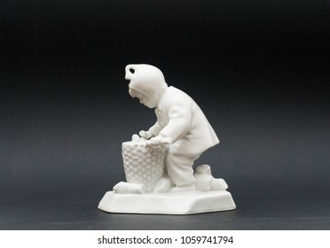 Little boy collecting wood - porcelain figurine isolated
